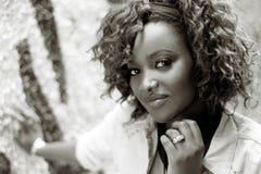 Schöne schwarze Frau im städtischen Hintergrund mit dem roten Haar Lizenzfreie Stockfotografie