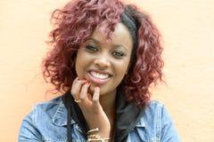 Schöne schwarze Frau im städtischen Hintergrund mit dem roten Haar Stockbild