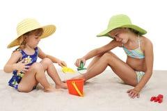 Schöne Schwestern in den Strand-Hüten, die im Sand spielen Lizenzfreies Stockfoto