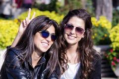 Schöne Schwestern, die in einem Park, im Lächeln und im Umarmen sitzen Stockbilder