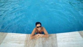 Schöne Schwimmen der jungen Frau und Lächeln in einem Badekurortpool stock footage