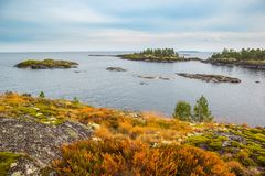 Schöne See-Felsen-Inseln gestalten roten Rusty Grass und grünen Moss Autumn Scenery Heavy Blue Sky landschaftlich stockbilder