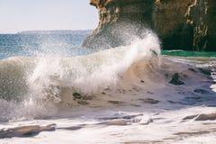 Schöne Seeansicht mit geheimem sandigem Strand unter Felsen und Klippe lizenzfreie stockbilder