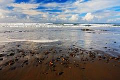 Schöne Seelandschaft Der Kiesel und der Sand setzen bei Sonnenaufgang, mit dunkelblauer Welle und weißen Wolken, Costa Rica-Küste Lizenzfreie Stockbilder