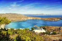 Schöne Seelandschaft, grüne Hügel, blauer Himmel und Azurblau wässern stockbild