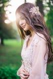 Schöne sexuelle Mädchen Brunettebraut, wenn draußen beige Spitzekleid, Dekoration auf dem Haar, in einem Park mit Bäumen, Birke t lizenzfreie stockbilder