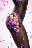 Schöne sexy Afrofrau mit Blumen auf Körper stockfotografie