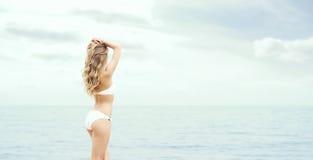 Schöne, sexy blonde Aufstellung auf dem Strand Stockbilder