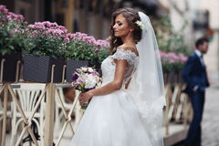 Schöne sexy blonde Braut im eleganten weißen Kleid mit Blumenstrauß Stockfotos