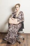 Schöne sexy blonde Frau, die auf dem Stuhl hält Modetasche sitzt Lizenzfreies Stockfoto