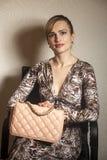 Schöne sexy blonde Frau, die auf dem Stuhl hält Modetasche sitzt Stockfotos