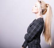 Schöne sexy blonde Frauenhaltung gegen Studiohintergrund Stockfotografie