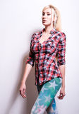 Schöne sexy blonde Frauenhaltung gegen Studiohintergrund Stockfoto