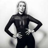 Schöne sexy blonde Frauenhaltung gegen Studiohintergrund Schwarz-weißes Foto Stockfoto