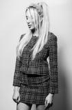 Schöne sexy blonde Frauenhaltung gegen Studiohintergrund Schwarz-weißes Foto Lizenzfreies Stockfoto