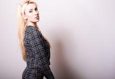 Schöne sexy blonde Frauenhaltung gegen Studiohintergrund Schwarz-weißes Foto Stockfotografie