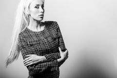 Schöne sexy blonde Frauenhaltung gegen Studiohintergrund Schwarz-weißes Foto Stockbild