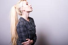 Schöne sexy blonde Frauenhaltung gegen Studiohintergrund Schwarz-weißes Foto Lizenzfreie Stockfotos