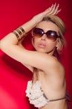 Schöne sexy blonde junge Frau im Bikini auf Rot Lizenzfreies Stockfoto