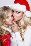 Schöne sexy blonde weibliche vorbildliche Mutter und Tochter gekleidet als Santa Claus in einer roten Kappe Stockbild