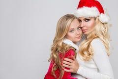 Schöne sexy blonde weibliche vorbildliche Mutter und Tochter gekleidet als Santa Claus in einer roten Kappe mit am Weiß Lizenzfreies Stockfoto