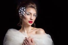 Schöne sexy Braut der eleganten Frau mit rotem Lippenstift mit einer schönen stilvollen Frisur mit Schleier in den Farben auf dem Stockfotos