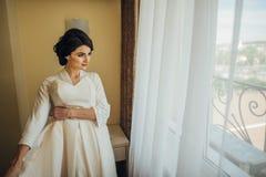 Schöne sexy Braut im weißen Kleid, das unter Vorhang aufwirft lizenzfreies stockbild