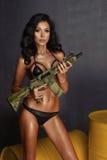Schöne sexy Brunette Frau, die Pistole hält stockfoto