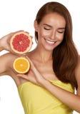 Schöne sexy Brunettefrau mit Zitrusfrucht auf einem weißen Hintergrund, gesundes Lebensmittel, geschmackvolles Lebensmittel, orga Lizenzfreie Stockbilder