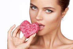Schöne sexy Brunettefrauenessenkuchenform des Herzens auf einem weißen Hintergrund, gesundes Lebensmittel, geschmackvoller, organ Stockbild