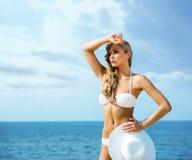 Schöne, sexy, dünne Dame im anziehenden Bikini, der mit einem Hut aufwirft Lizenzfreies Stockbild