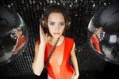 Schöne sexy Disco-DJ-Frau in der Wäsche umgeben durch discobal Lizenzfreie Stockfotos