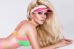Schöne sexy formschöne Blondine mit dem langen Haar liegt in einem bunten Lizenzfreie Stockbilder