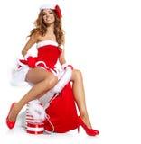 Schöne sexy Frau, die Weihnachtsmann-Kleidung trägt Stockfotografie