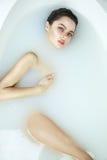 Schöne sexy Frau im Bad mit Milchbadekurort-Kosmetikkörper Stockfotos