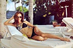 Schöne sexy Frau im Bikini, der im Liege sich entspannt stockbilder