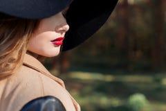 Schöne sexy Frau im eleganten schwarzen Hut mit großen Feldern und im hellen roten Lippenstift auf ihren Lippen Stockfotografie