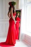 Schöne sexy Frau im roten Kleid des eleganten langen Abends, das im Spiegel nahe bei dem Fenster mit einem Weihnachtskranz auf ih Lizenzfreie Stockfotos