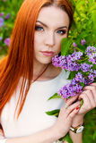 Schöne Frau mit dem brennenden Regimehaar mit Augen eines Fox im Garten mit Fliedern Lizenzfreie Stockfotos