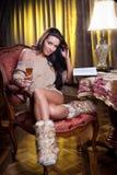 Schöne sexy Frau mit dem Glas Wein ein Buch lesend, das auf Stuhl sitzt Lizenzfreie Stockfotos