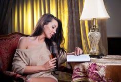 Schöne sexy Frau mit dem Glas Wein ein Buch lesend, das auf Stuhl sitzt Lizenzfreies Stockfoto