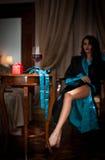 Schöne sexy Frau mit dem Glas Wein sitzend auf Stuhl. Porträt einer Frau mit dem langen gelockten Haar, welches die Herausforderun Stockbild
