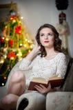 Schöne sexy Frau mit Weihnachtsbaum in der Hintergrundlesung ein Buch, das auf Stuhl sitzt. Porträt einer Frau, die eine angenehme Stockfoto