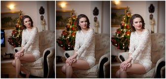Schöne sexy Frau mit Weihnachtsbaum im Hintergrund, der auf elegantem Stuhl in der gemütlichen Landschaft sitzt Porträt des Mädch Stockfoto