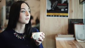 Schöne sexy Frau sitzt in einem Café, das er einen Cappuccino trinkt und schaut träumerisch heraus das Fenster stock video