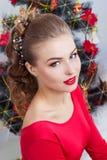 Schöne sexy glückliche lächelnde junge Frau im Abendkleid mit hellem Make-up mit dem roten Lippenstift, der nahe dem Weihnachtsba Stockbilder