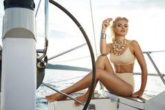 Schöne sexy junge Blondine, ein Boot auf das Wasser reiten, Route, schönes Make-up, Kleidung, Sommer, Sonne, perfekte Körper-FI lizenzfreies stockbild