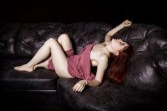 Schöne sexy junge Frau der Rothaarigen, die auf einem schwarzen ledernen Sofa auf einem schwarzen Hintergrund liegt Stockfotografie