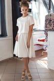 Schöne sexy junge Frau im schönen modernen weißen Kleid im Studio, das für das Kameramodetrieb für die Kleidung aufwirft Stockbilder