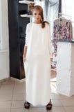 Schöne sexy junge Frau im schönen modernen weißen Kleid im Studio, das für das Kameramodetrieb für die Kleidung aufwirft Stockbild